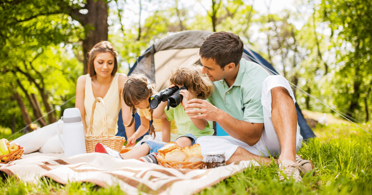a family sitting in front of their tent at a campsite