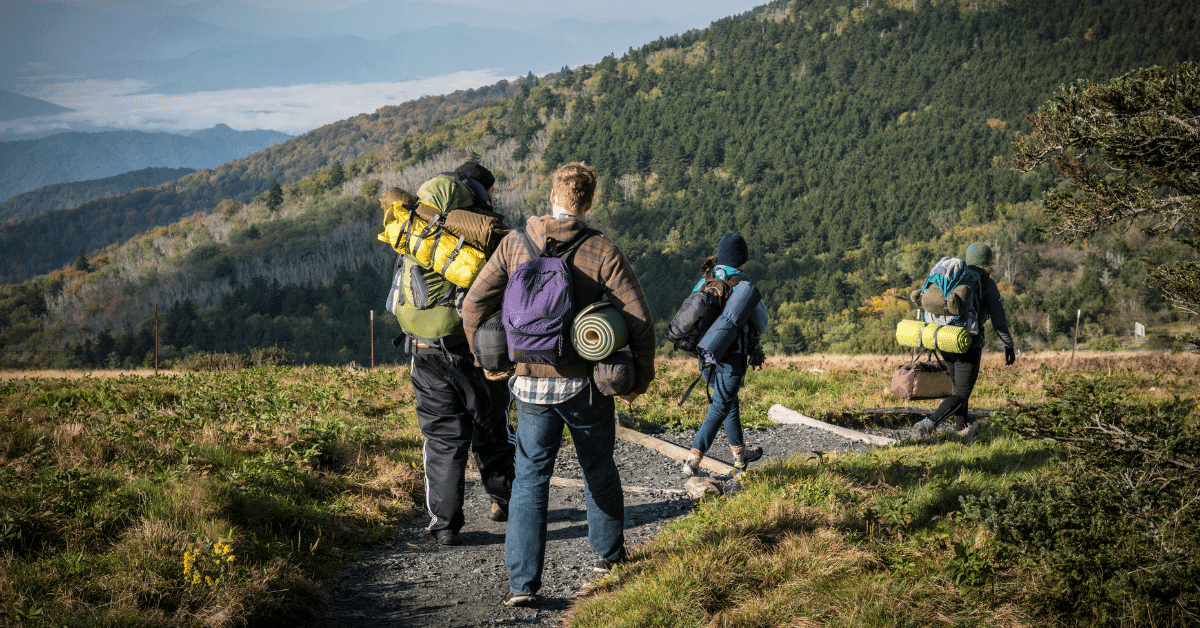 a group of people carrying their camping gear to a campsite