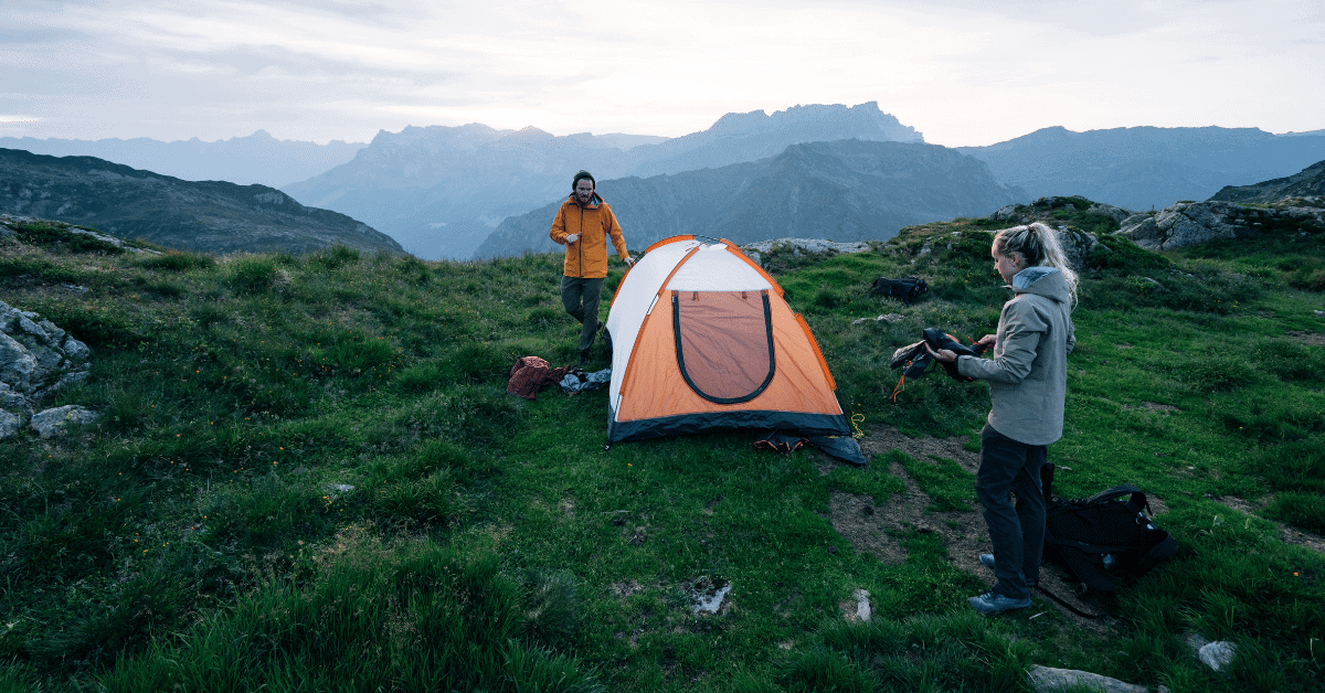 a man and a woman at a campsite in the wild