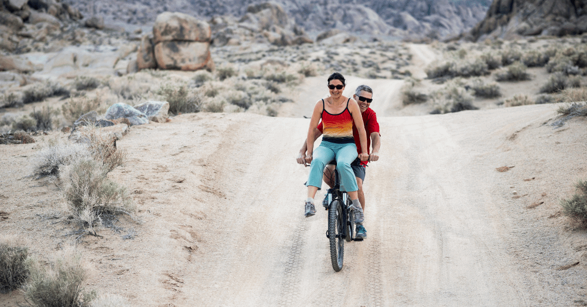 a man and a woman riding a bicycle through a desert landscape