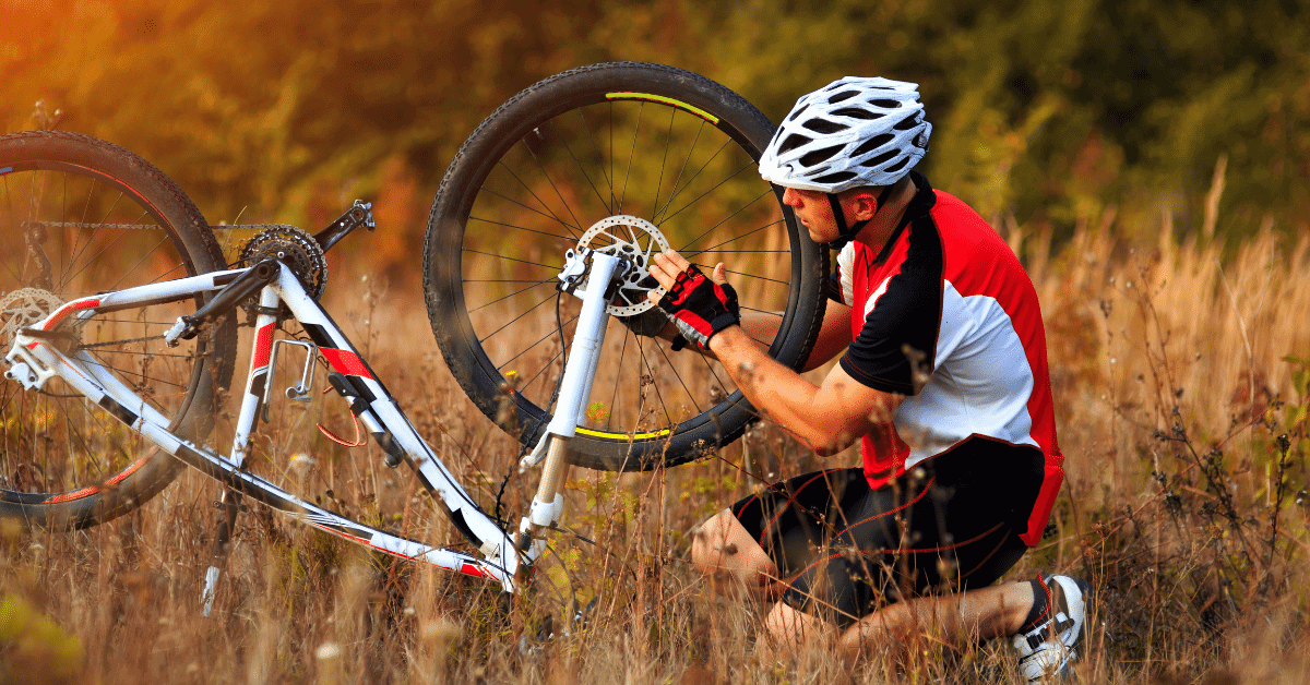 a man repairing his bicycle on a trail