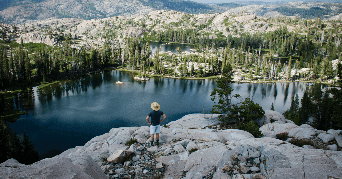 a man standing on a cliff above a lake