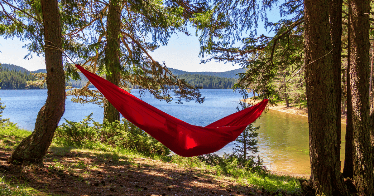 a person lying in a red hammock beside a lake