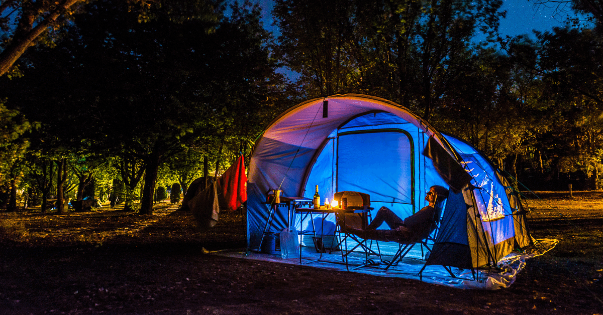 a person relaxing in front of a tent at night