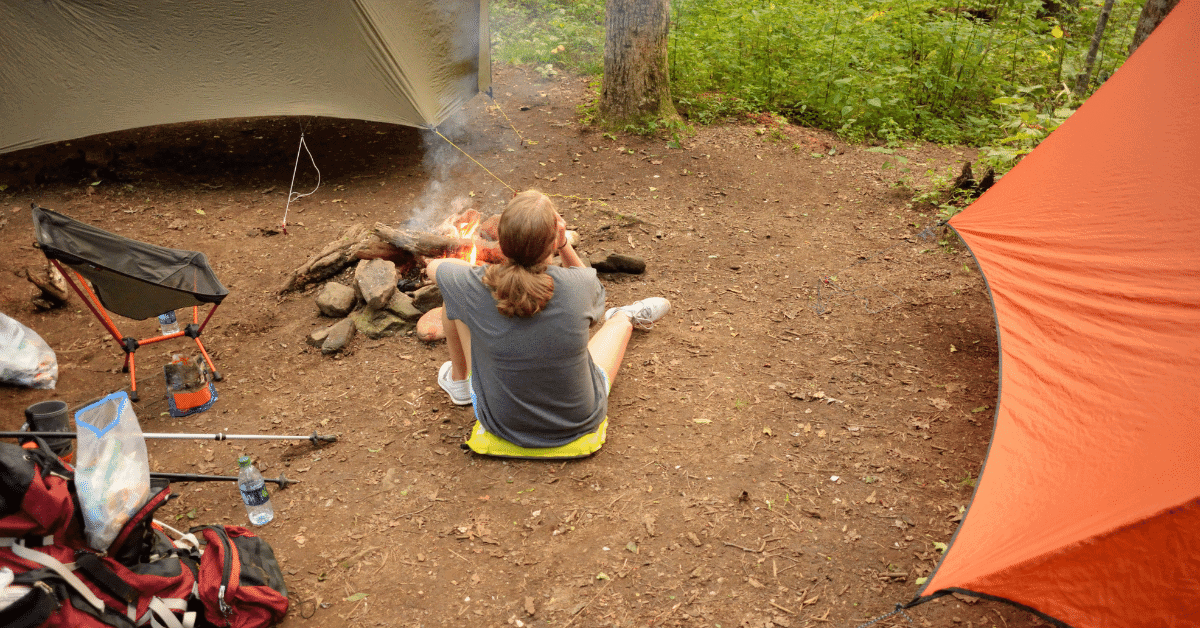 a person sitting at a campsite between two tarp shelters