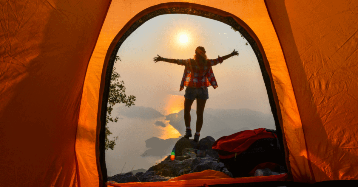 a person standing in front of a tent on a cliff overlooking the sea