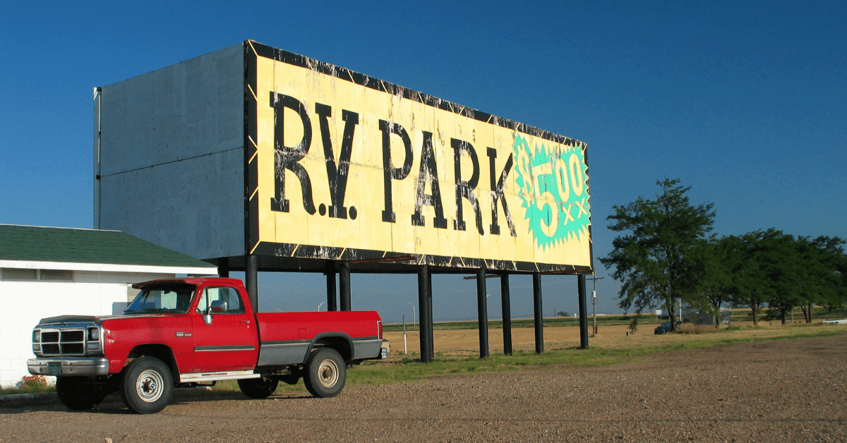 a pickup truck parked in front of an rv park sign