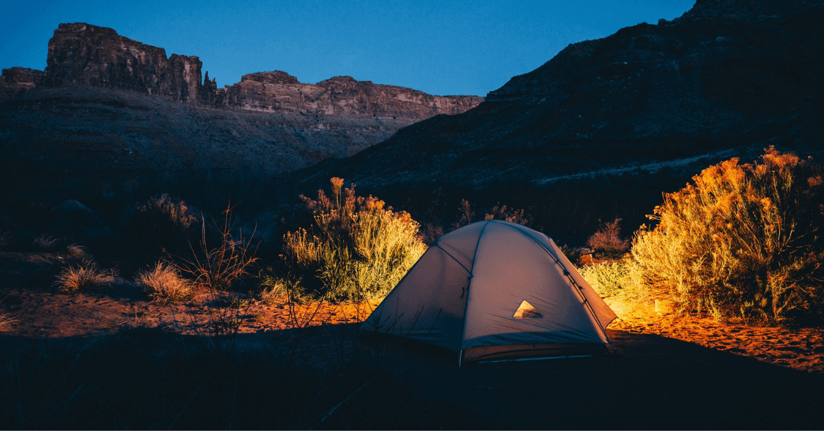 a tent in the desert at nighttime