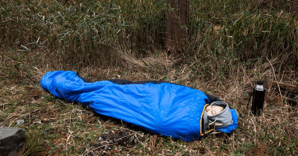 a woman cowboy camping in a blue sleeping bag