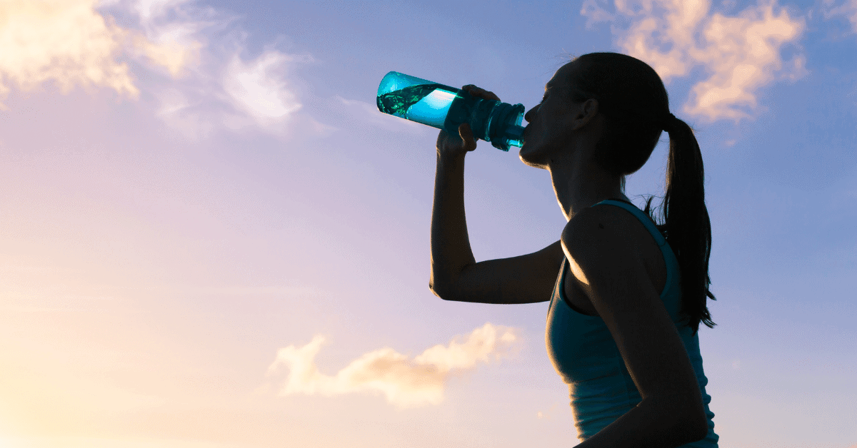 a woman drinking water from a water bottle