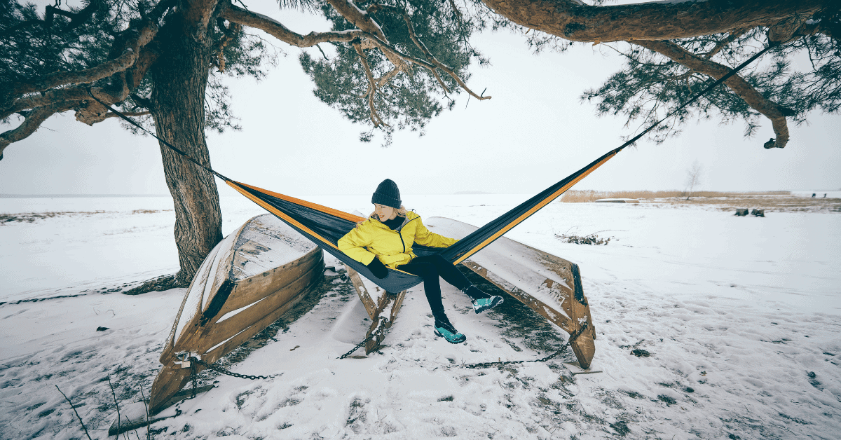 a woman in a hammock in the snow