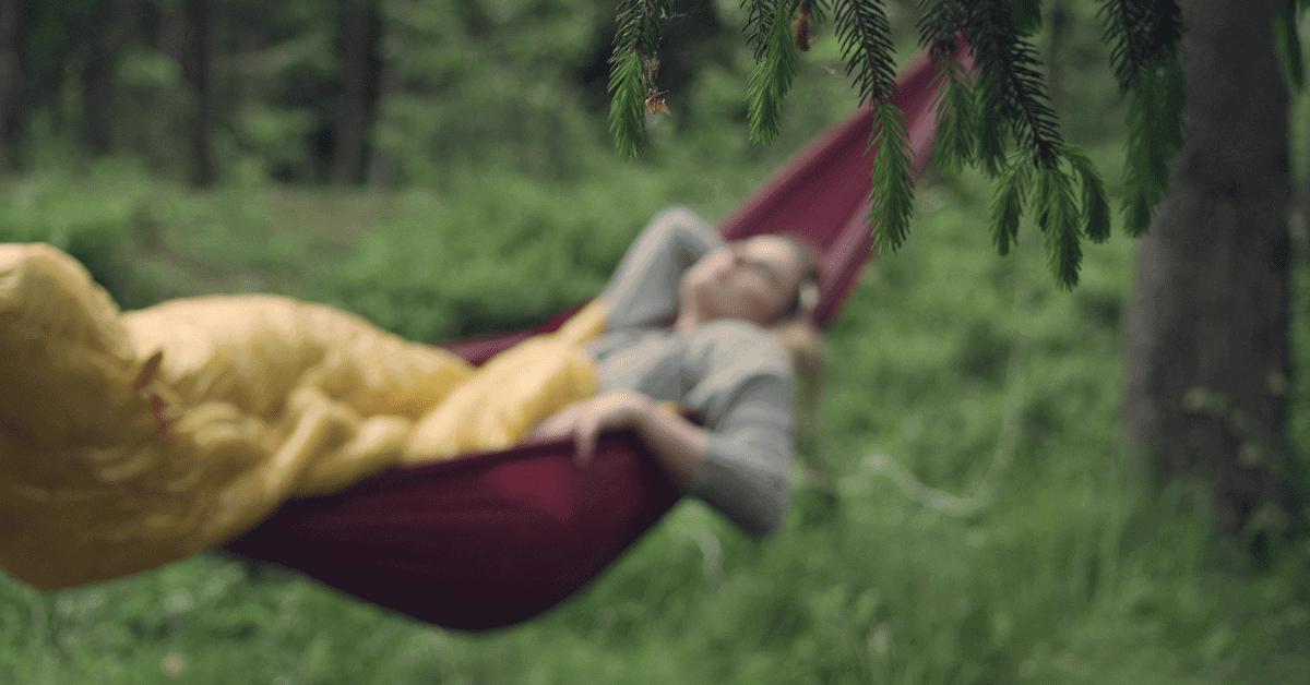 a woman in a hammock with a sleeping bag