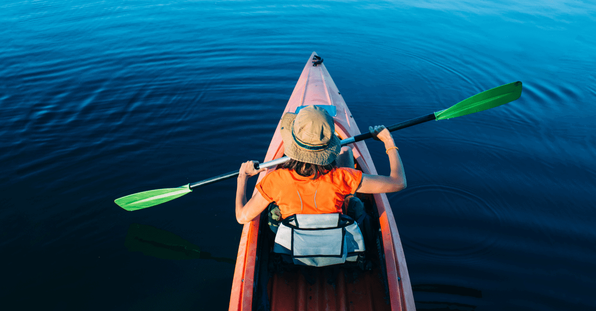 a woman kayaking in an orange shirt and a bucket hat