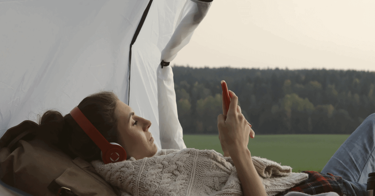 a woman resting and listening to music in a tent