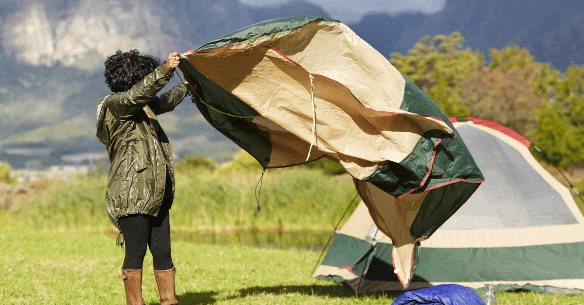 a woman shaking out a tent footprint