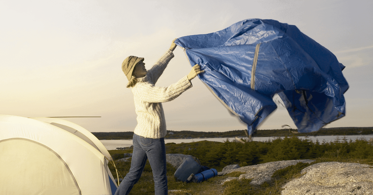 a woman standing by a tent shaking out a camping tarp