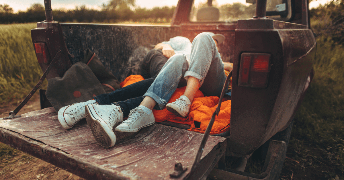 a young couple lying in a truck bed