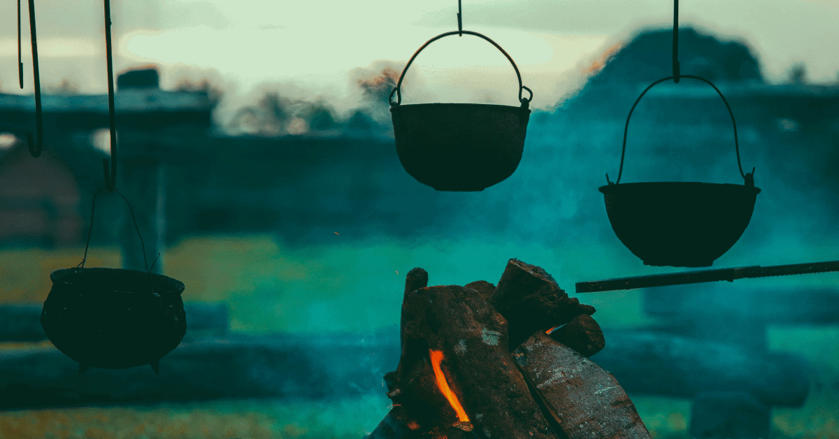 several pots hanging from a cowboy cooking stand