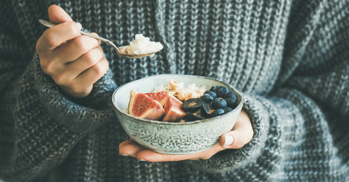 someone holding a bowl of porridge with figs and blueberries