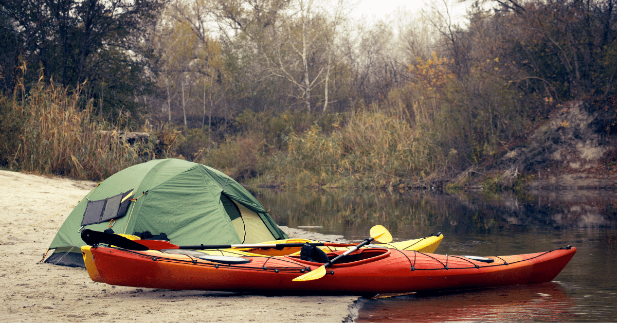 two kayaks and a tent on a riverbank