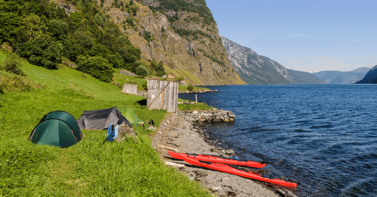 two red kayaks and three tents on a lake