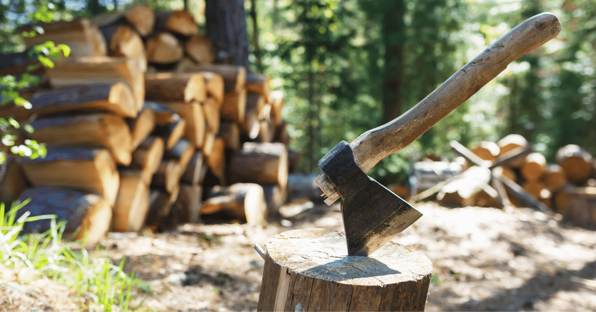 hatchet in a log with firewood in the background