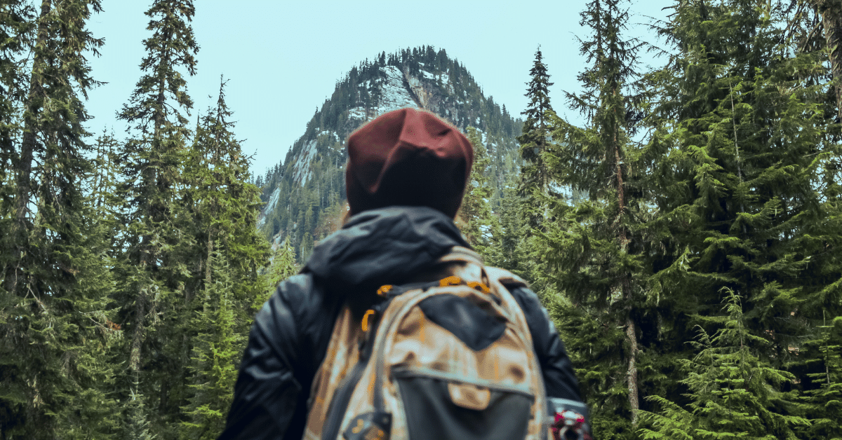 hiker standing in front of a mountain