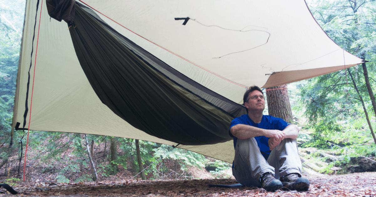 man sitting next to hammock with a ridgeline