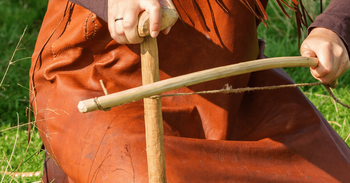 woman using a bow drill to start a fire