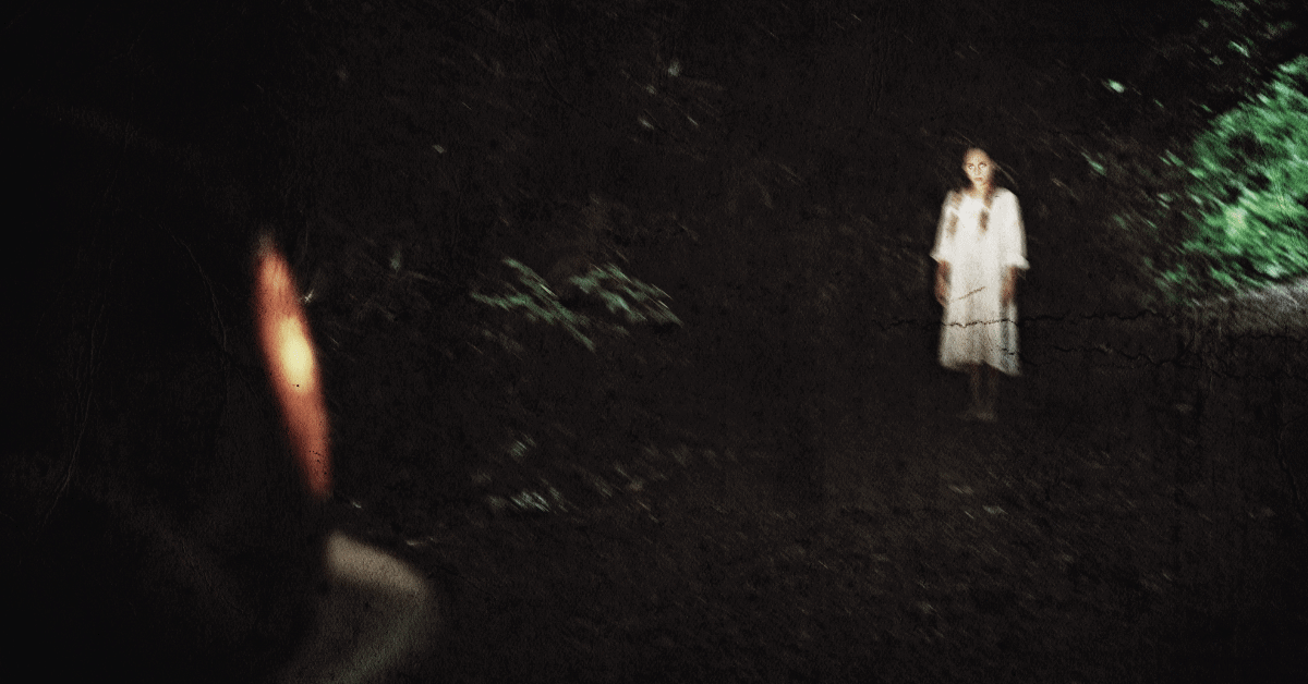 creepy girl in white dress standing in the headlights