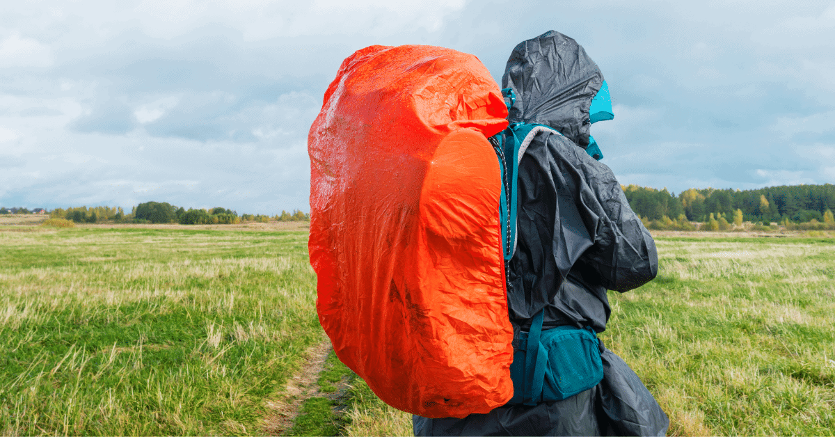 hiker wearing rain gear and a backpack with a rain cover