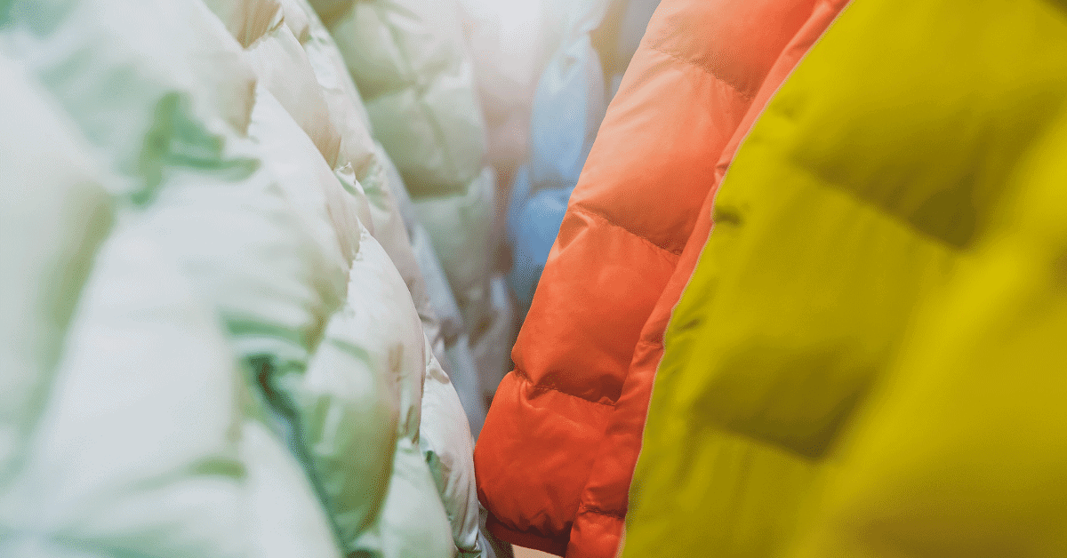 lots of colorful down jackets hanging on a rack