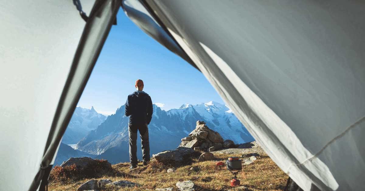 man standing in front of a tent looking out at a snowy mountain view