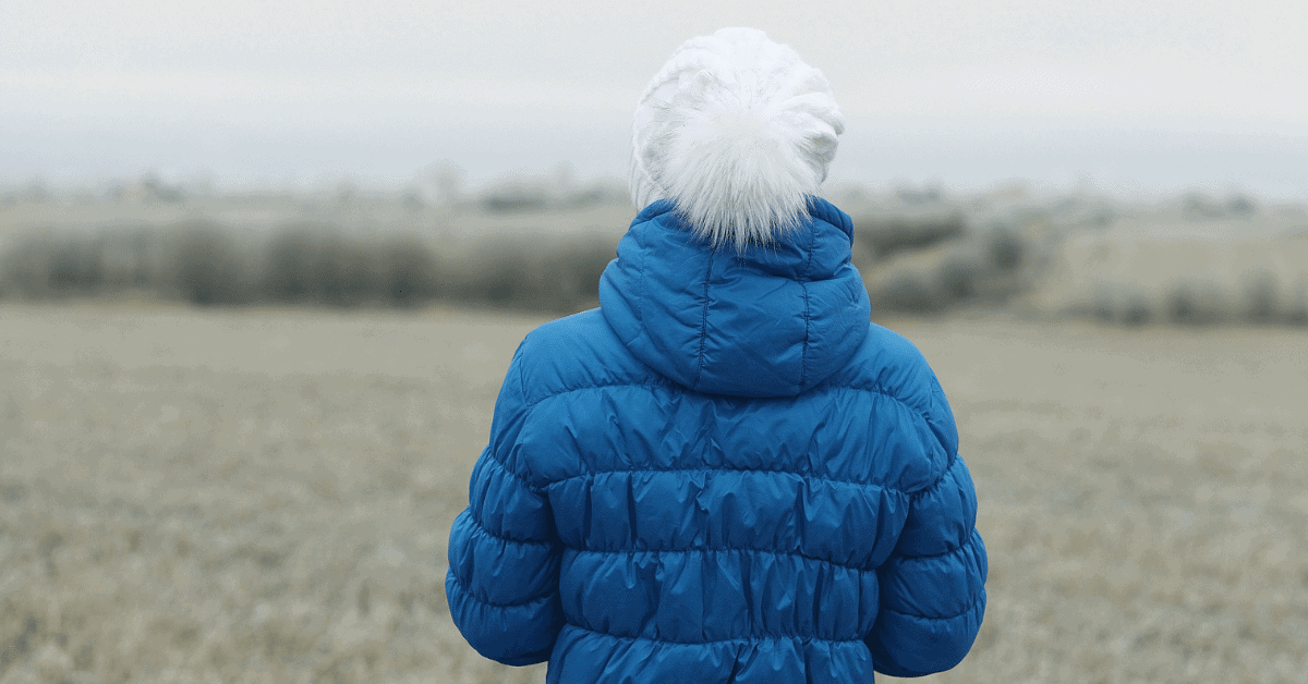 person wearing blue down jacket and white hat with pompom