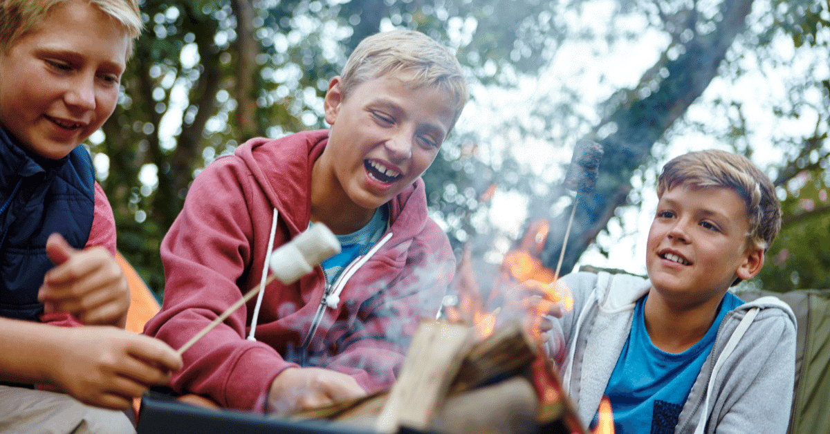 young boys toasting marshmallows on the campfire