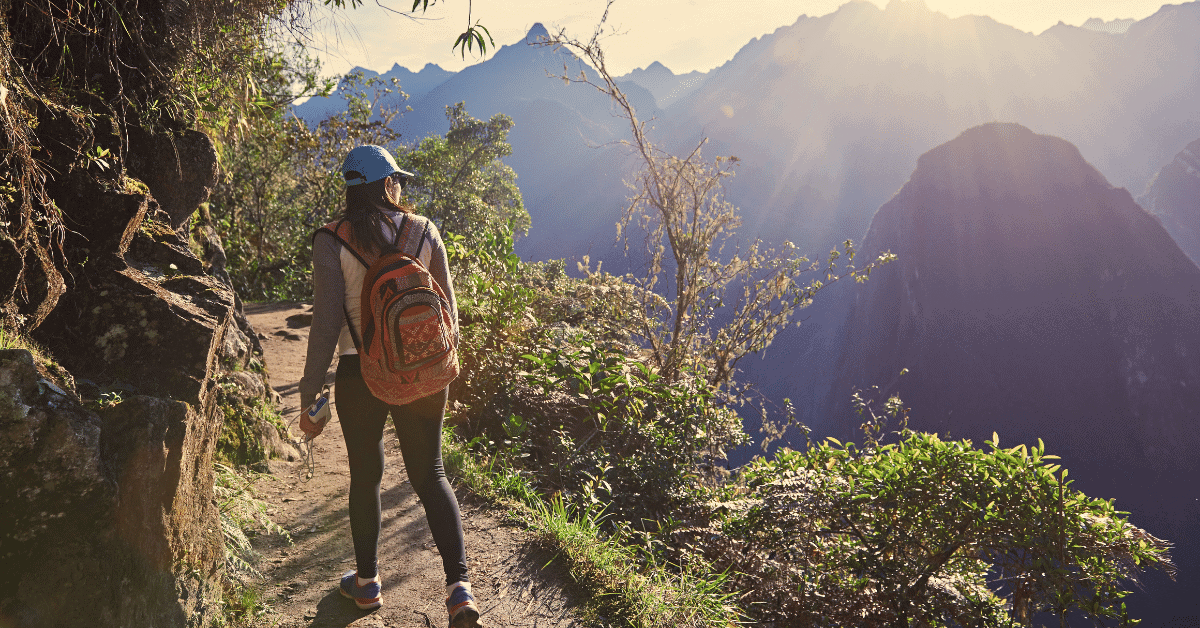 woman day hiking along a trail on a mountain