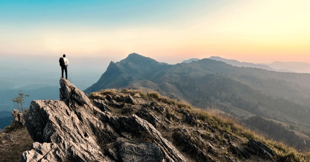 man standing a mountain peak
