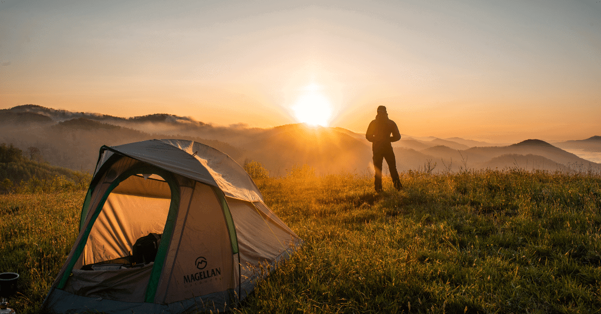 person standing in front of a tent in nature at sunset