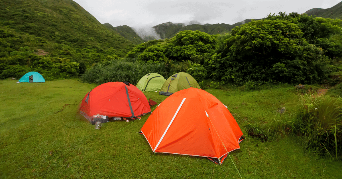 several multicolored tents in a green hilly landscape