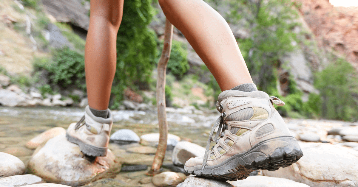 woman crossing a stream wearing hiking boots