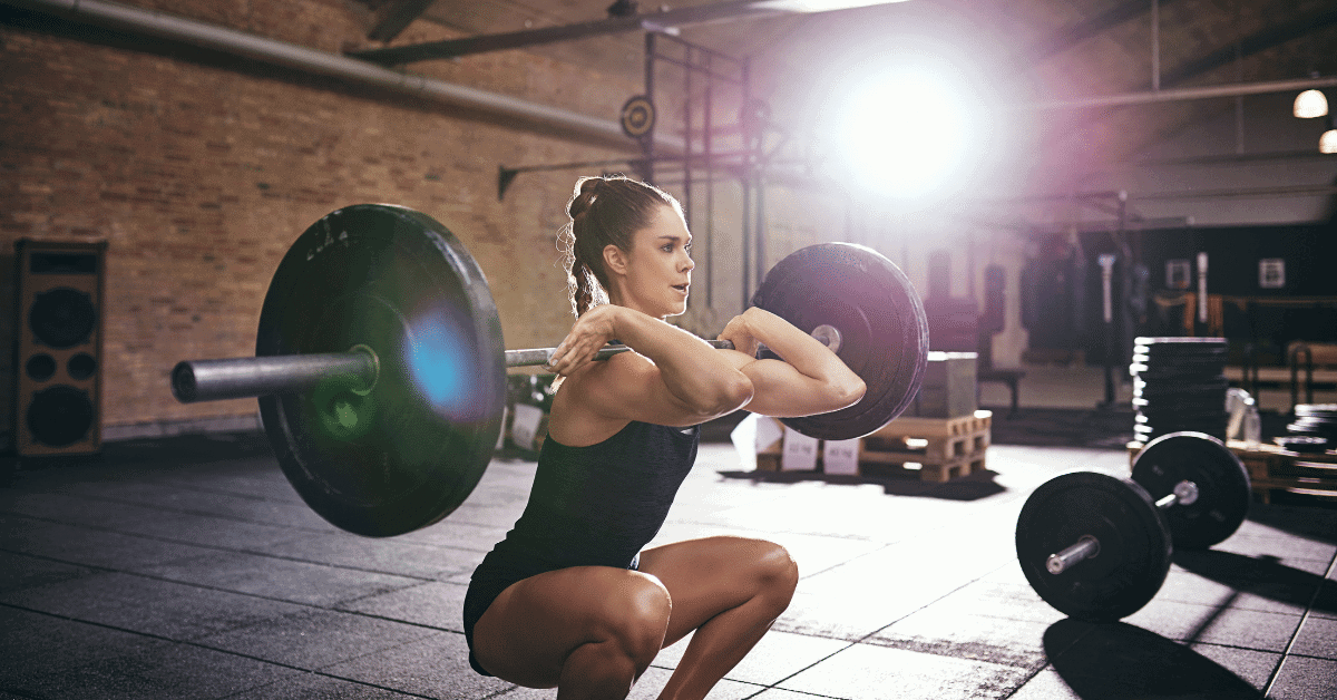 woman doing front squats at the gym