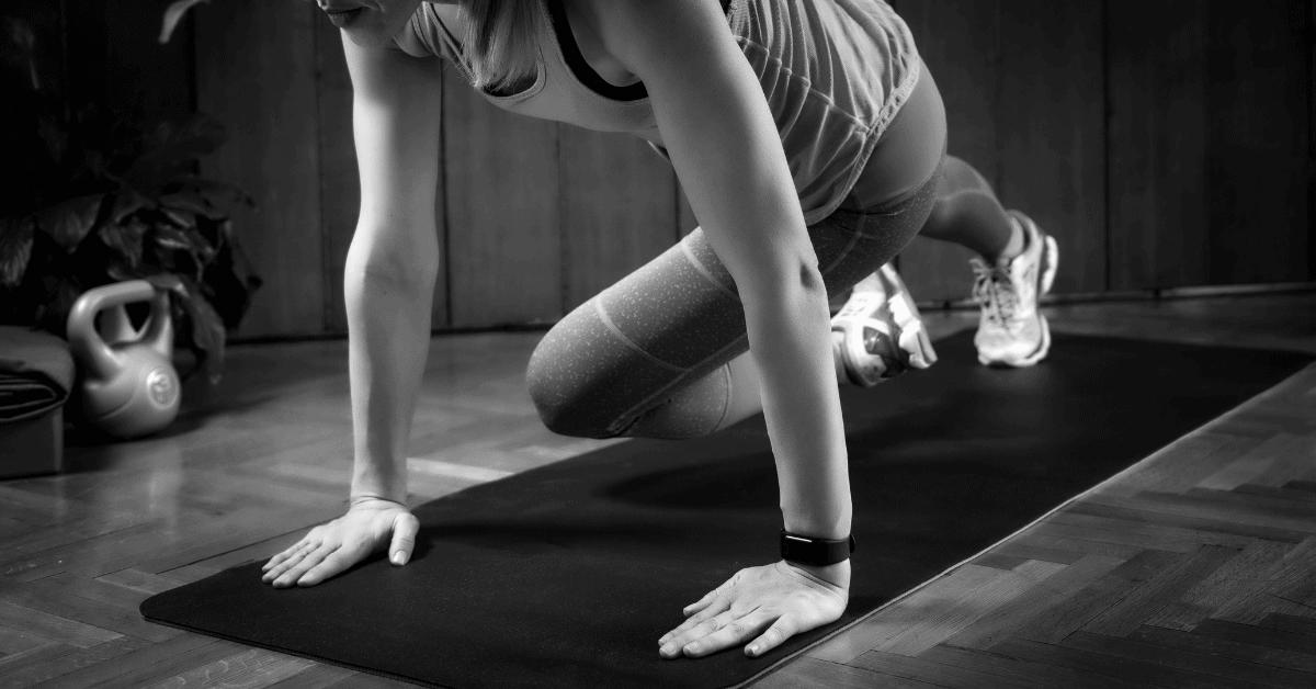 woman doing mountain climbers on a yoga mat