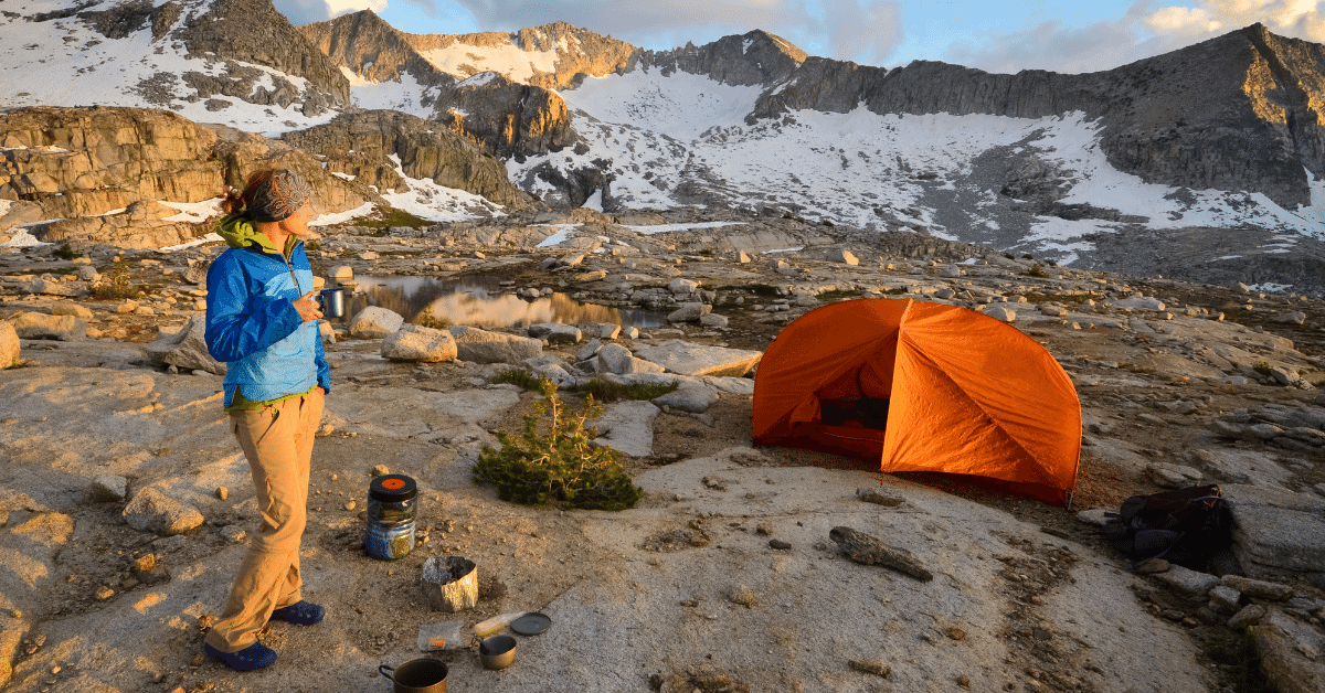 woman enjoying a hot drink by her tent in the backcountry